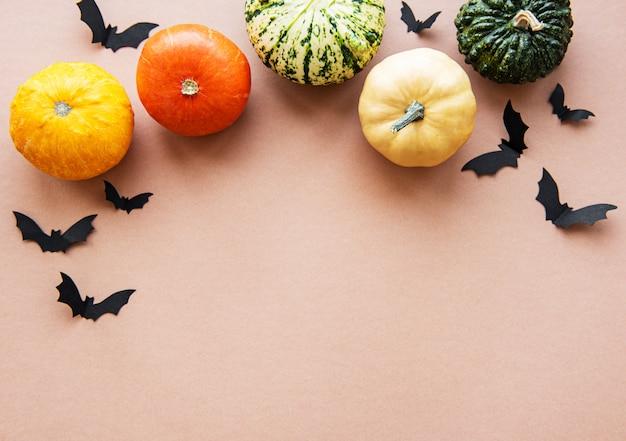 Murciélagos de halloween y calabazas sobre fondo marrón