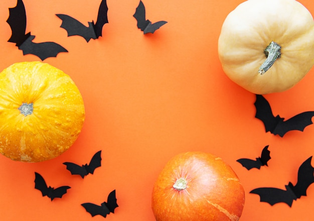 Murciélagos de halloween y calabazas sobre fondo naranja