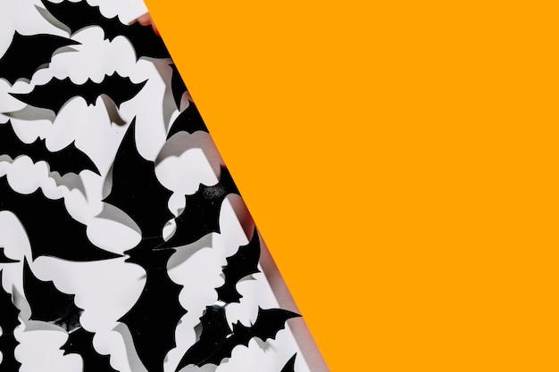 Murciélagos negros de halloween con una gran pieza de papel naranja
