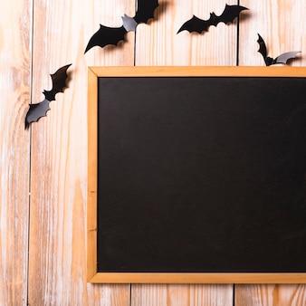 Murciélagos de papel cerca de la pizarra