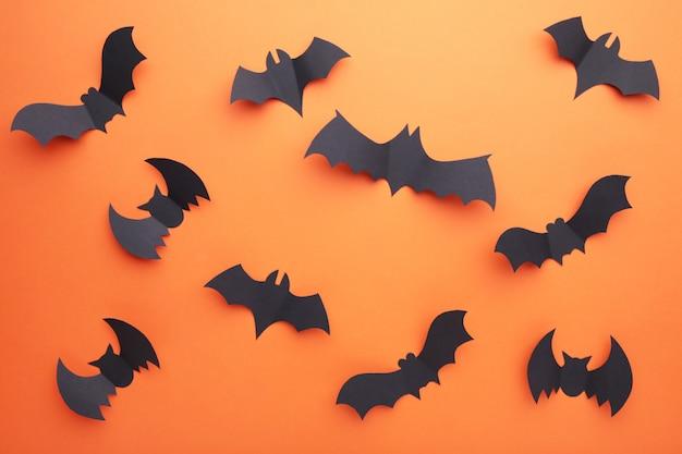 Murciélagos de papel de halloween sobre fondo naranja. festividad de todos los santos