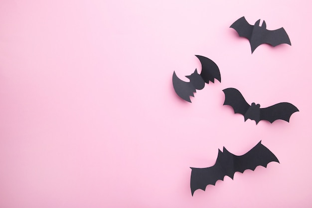 Murciélagos de papel de halloween sobre fondo rosa pastel. halloween, marco