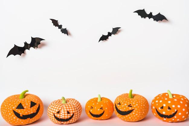 Murciélagos de papel sobre jack-o-lanterns de juguete
