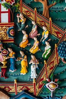 Muro decorado que cuenta la historia de buda en el arte de bután dentro del monasterio real de bután.