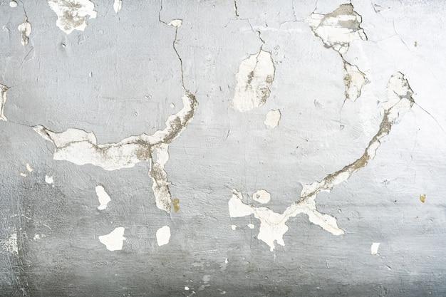 Muro de hormigón agrietado pintado con textura color plata.