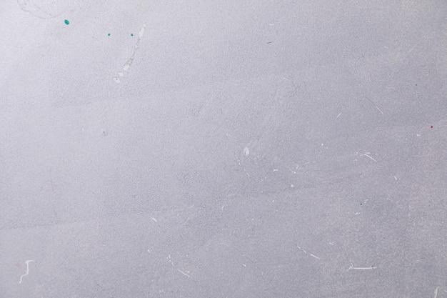 Muro de hormigón blanco con algunas manchas de pintura.