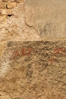 Muro de hormigón con ladrillos y superficie desgastada.
