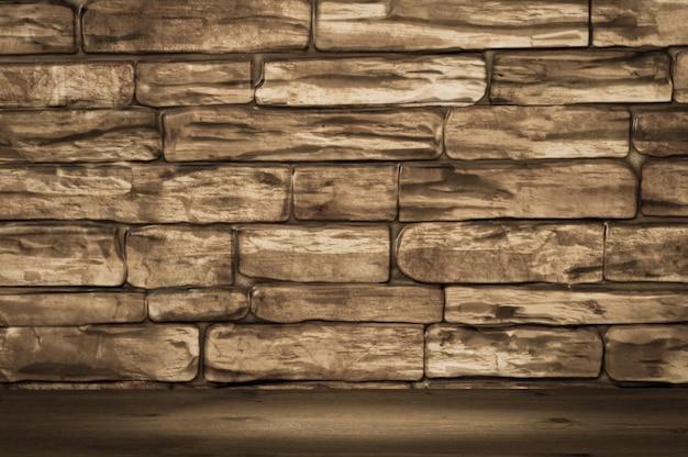 Muro de ladrillos grandes de color marrón y tablas de madera con iluminación puntual.