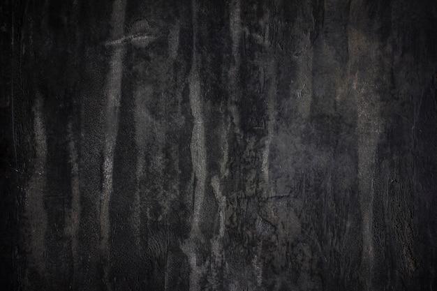 El muro de piedra de hormigón con textura de fondo negro.
