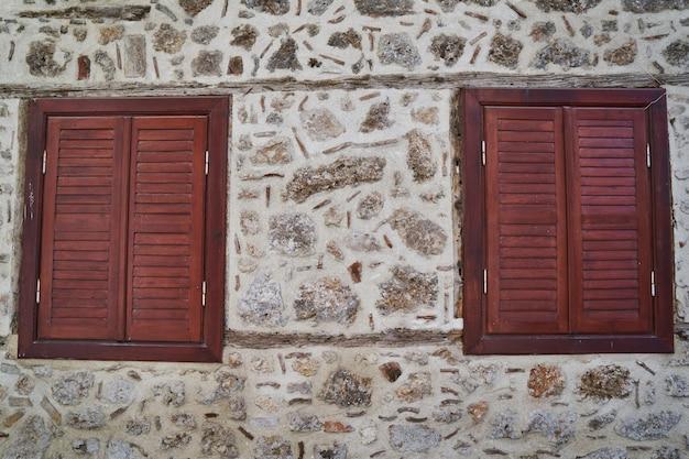 Muro de piedra y viejas ventanas de madera