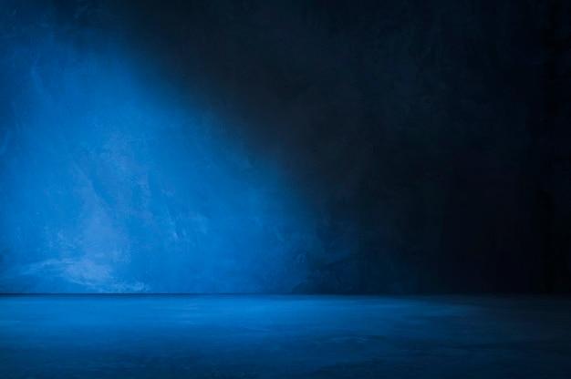 Muro y piso de concreto azul con fondos de luz y sombra, uso para exhibición de productos para presentación y diseño de banner de portada.