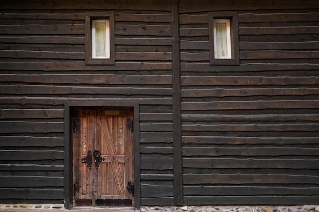 Muro de vigas de madera oscura, pequeñas ventanas y puerta vintage.