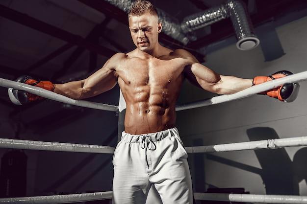 Muscular boxeador profesional descansando sobre las cuerdas en la esquina del ring mientras entrena para el próximo partido