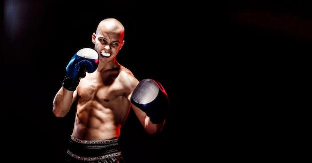 Muscular luchador de muay thai golpeando en la oscuridad