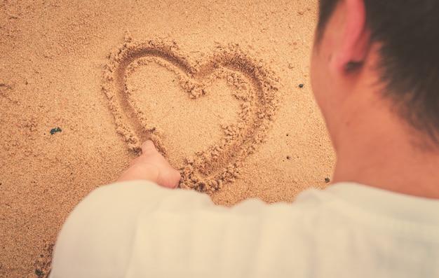 Músculo hombre dibujar corazón en la arena. luz internacional del sol y tono de la vendimia.