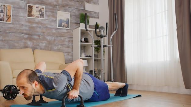 Músculo del pecho de entrenamiento atlético hombre haciendo flexiones en casa en estera de yoga.