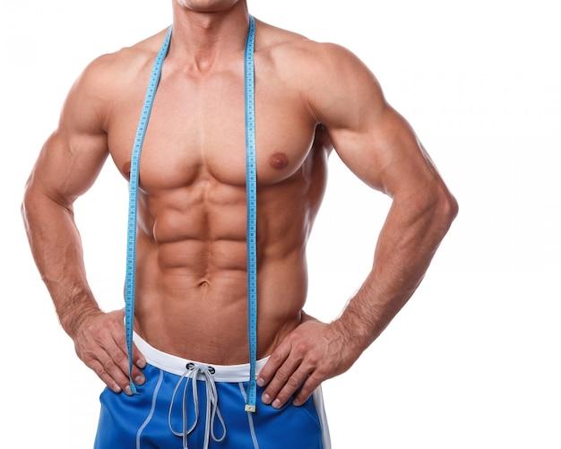 Musculoso torso masculino y cinta métrica