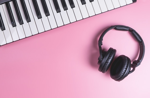 Music studio keyboard and headphone en el espacio de la copia rosa