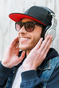 La musica es mi pasion. feliz joven en auriculares sonriendo mientras se inclina contra la pared de hormigón