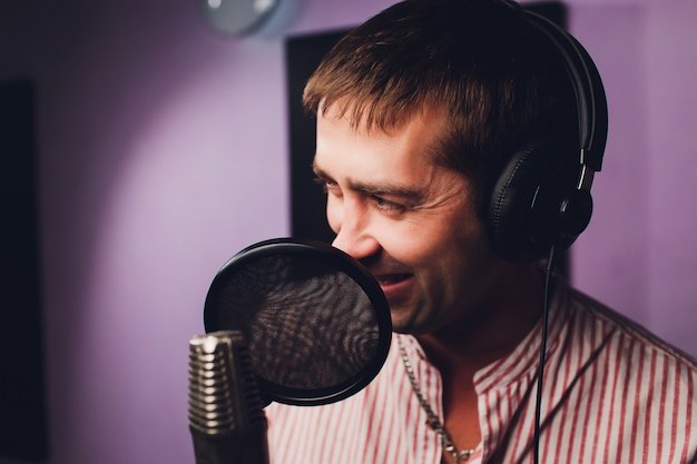 Música, espectáculo, personas y concepto de voz: cantante masculino con auriculares y micrófono cantando una canción en el estudio de grabación de sonido.