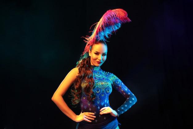 Música. hermosa mujer joven en carnaval, elegante disfraz de mascarada con plumas sobre fondo negro en luz de neón. copyspace para anuncio. celebración de fiestas, baile, moda. tiempo festivo, fiesta.