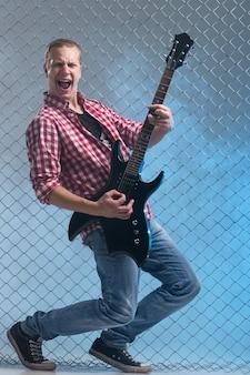 Música. joven músico con una guitarra en la valla de la pared