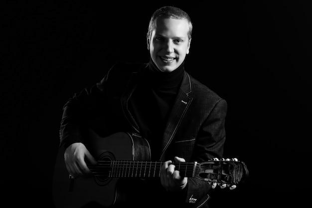 Música. joven músico en traje negro con una guitarra