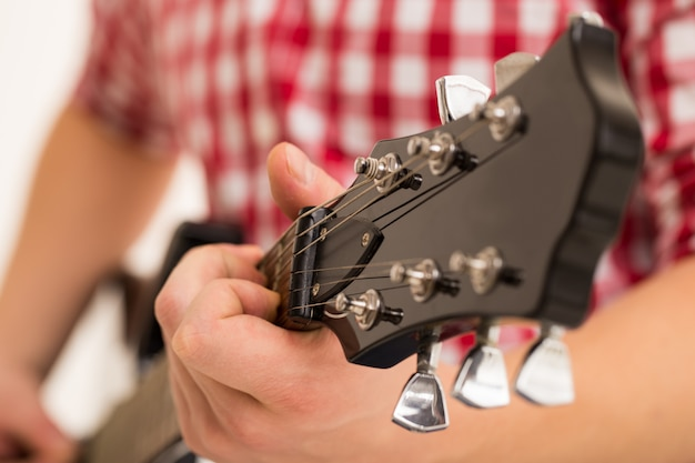 Música, primer plano. músico sosteniendo una guitarra de madera