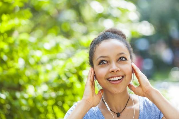 Música que escucha hermosa de la mujer joven de la raza mixta con los auriculares en el parque