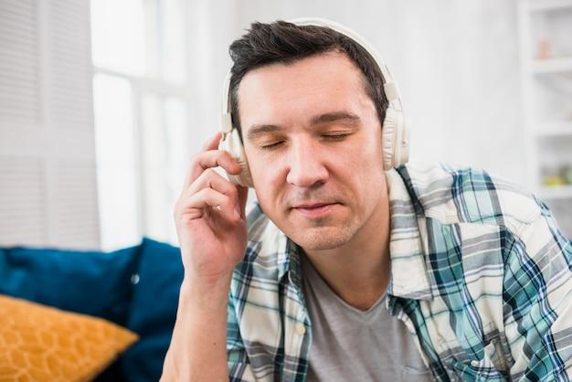 Música que escucha del hombre en auriculares en el sofá