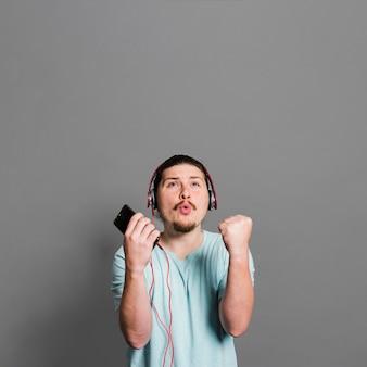 Música que escucha del hombre joven en el auricular que pone mala cara contra la pared gris
