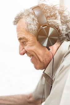 Música que escucha del hombre mayor en el auricular contra el fondo blanco