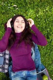 Música que escucha linda de la mujer joven con los auriculares