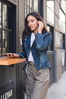 Música que escucha de moda de la mujer joven en el auricular a través del teléfono móvil