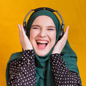 Música que escucha de la mujer árabe joven alegre en el auricular contra fondo amarillo