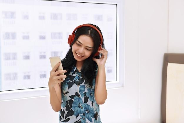 Música que escucha de la mujer asiática feliz con el auricular