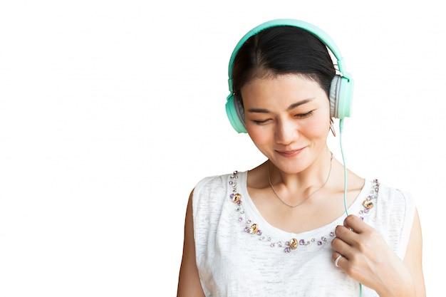 Música que escucha de la mujer asiática feliz por los auriculares aislados en el fondo blanco