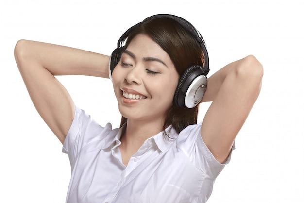 Música que escucha de la mujer asiática hermosa con el auricular