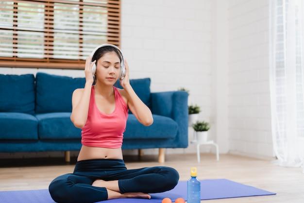Música que escucha de la mujer asiática joven mientras que practica yoga en sala de estar