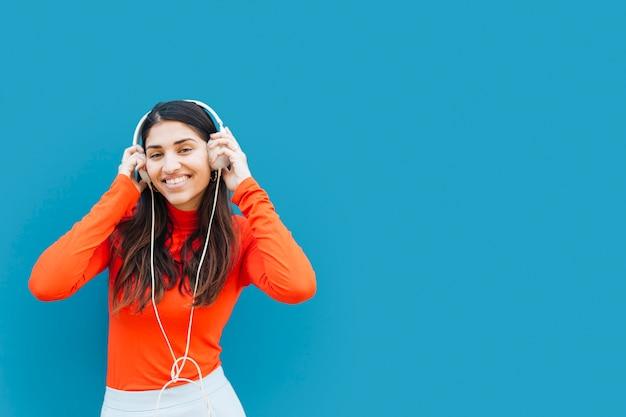 Música que escucha de la mujer bastante joven con el auricular