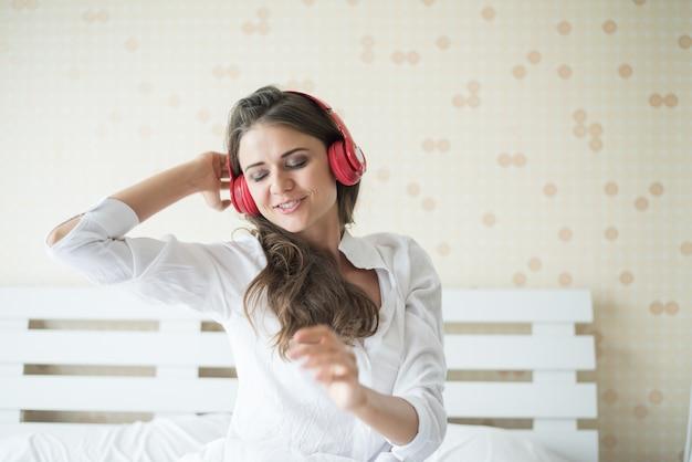 Música que escucha de la mujer hermosa en la mañana que se sienta en cama en casa
