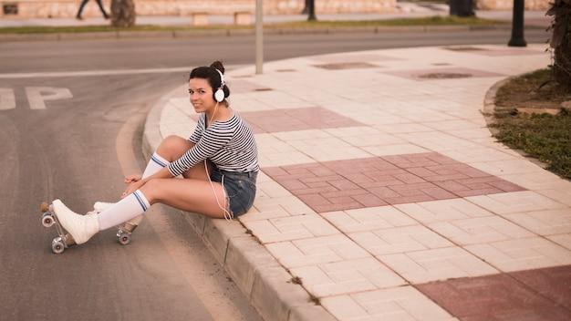 Música que escucha de la mujer joven en el auricular que se relaja en el camino