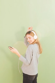 Música que escucha de la mujer joven en el auricular a través del baile del teléfono móvil contra fondo del verde menta