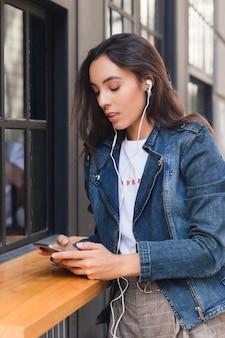 Música que escucha de la mujer joven en el auricular usando smartphone