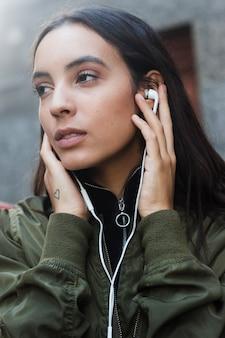 Música que escucha de la mujer joven en el auricular
