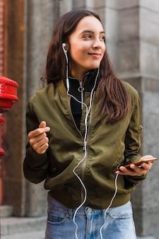Música que escucha de la mujer joven en la fijación del auricular al teléfono móvil