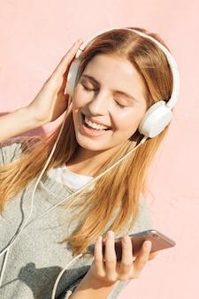 Música que escucha de la mujer joven en la fijación del auricular a través del teléfono móvil contra fondo rosado