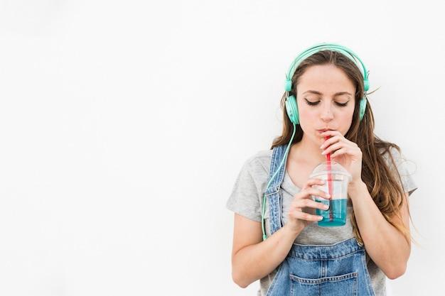 Música que escucha de la mujer joven en el jugo de consumición de los auriculares