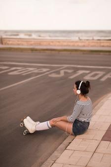 Música que escucha del patinador de sexo femenino joven en el auricular que se sienta en la acera por el borde de la carretera