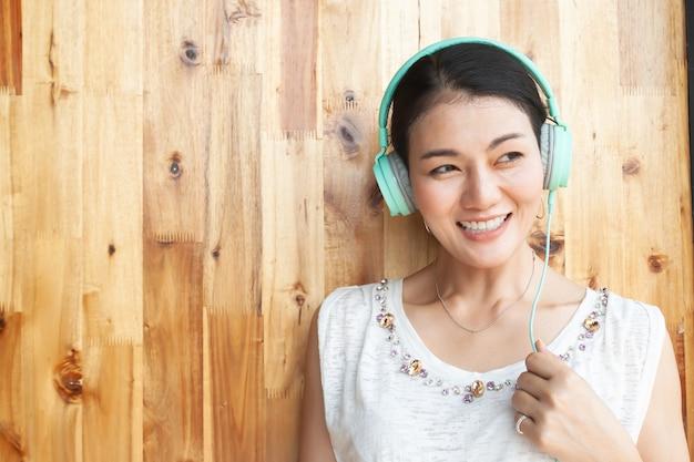 Música que escucha smilling feliz de la mujer asiática por los auriculares